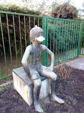 socha před budovou MŠ s rouškou